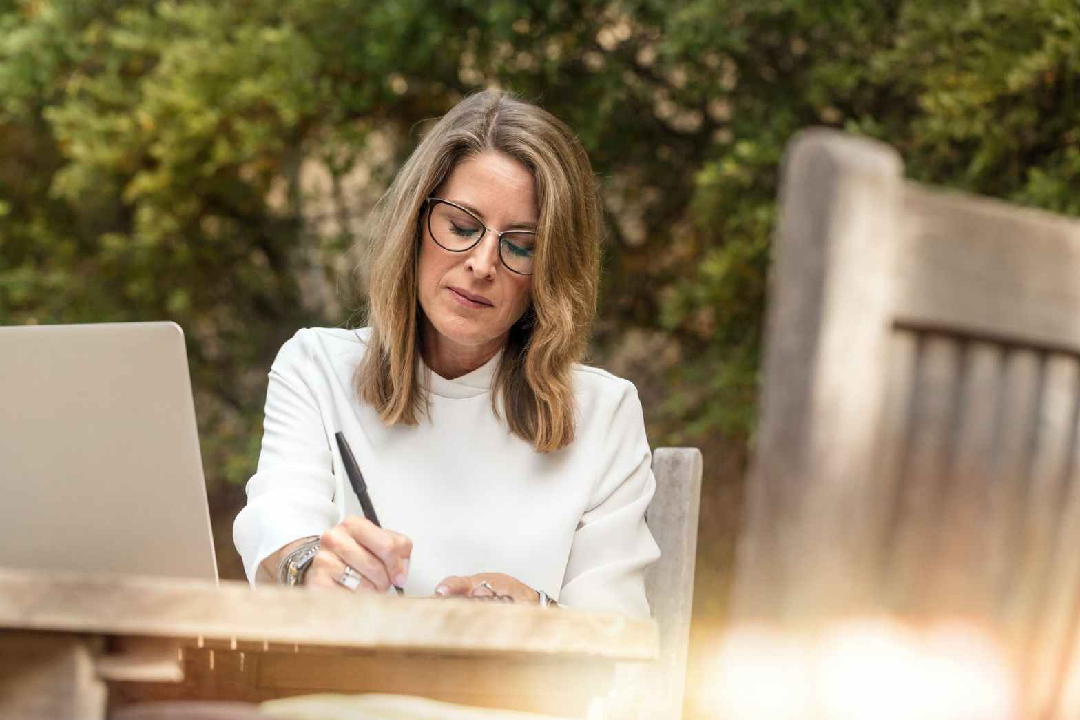 woman sitting on gray chair while writing on table