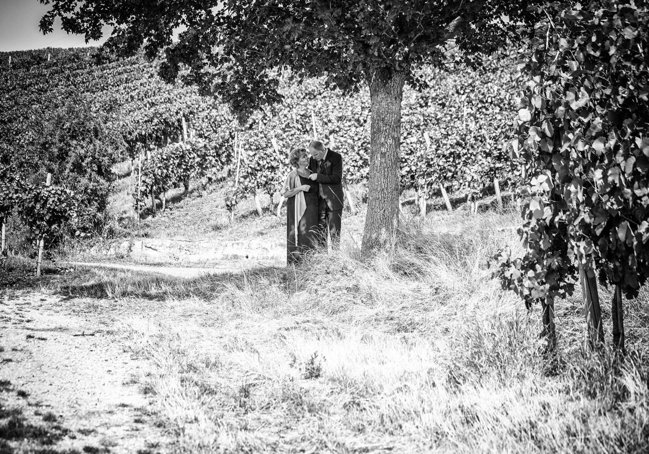 Brautpaarshooting in der Natur. Das verliebte Paar posiert auf einem Weinberg. Eine Schwarzweißaufnahme an einem Sommertag.