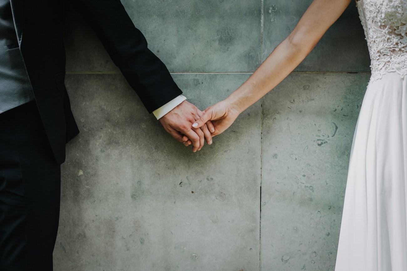 Hände eines Brautpaares vor einer Betonwand