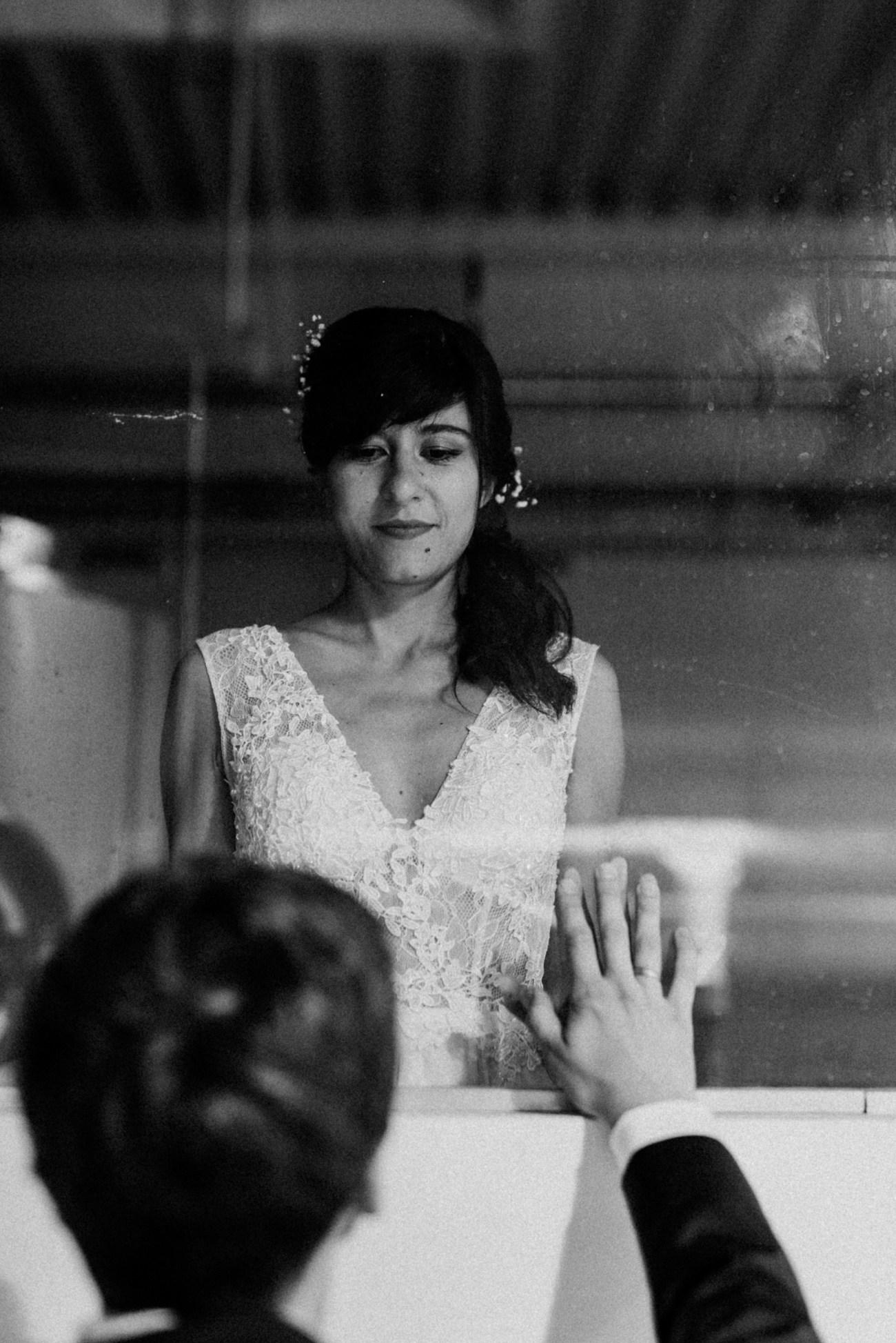 Eine Braut schaut durch ein Fenster zu Ihrem Bräutigam