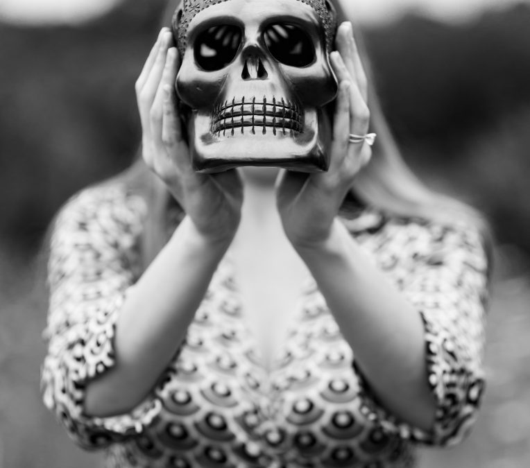 woman holding death mask, healing grief in menopause with homeoapathy