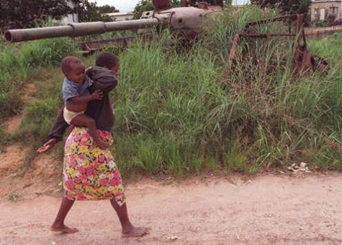 A woman adjusts her child on her back as she passes an abandoned tank along the road in the central Angolan town of Huambo, Wednesday 18 Febraury, 1998. This street marked the front-lines of a 55 day battle between government and rebel UNITA forces in 1993.(AP Photo/Adil Bradlow)