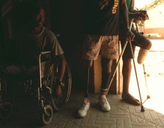 "Maimed combatants from Angola's 33 year civil war - known as ""Mutilados"" - hang around the doorway of their dormitory at an orthopedic centre in Luanda, Monday February 16, 1998, as they await the manufacture of custom made prostheses. (AP Photo/Adil Bradlow)"