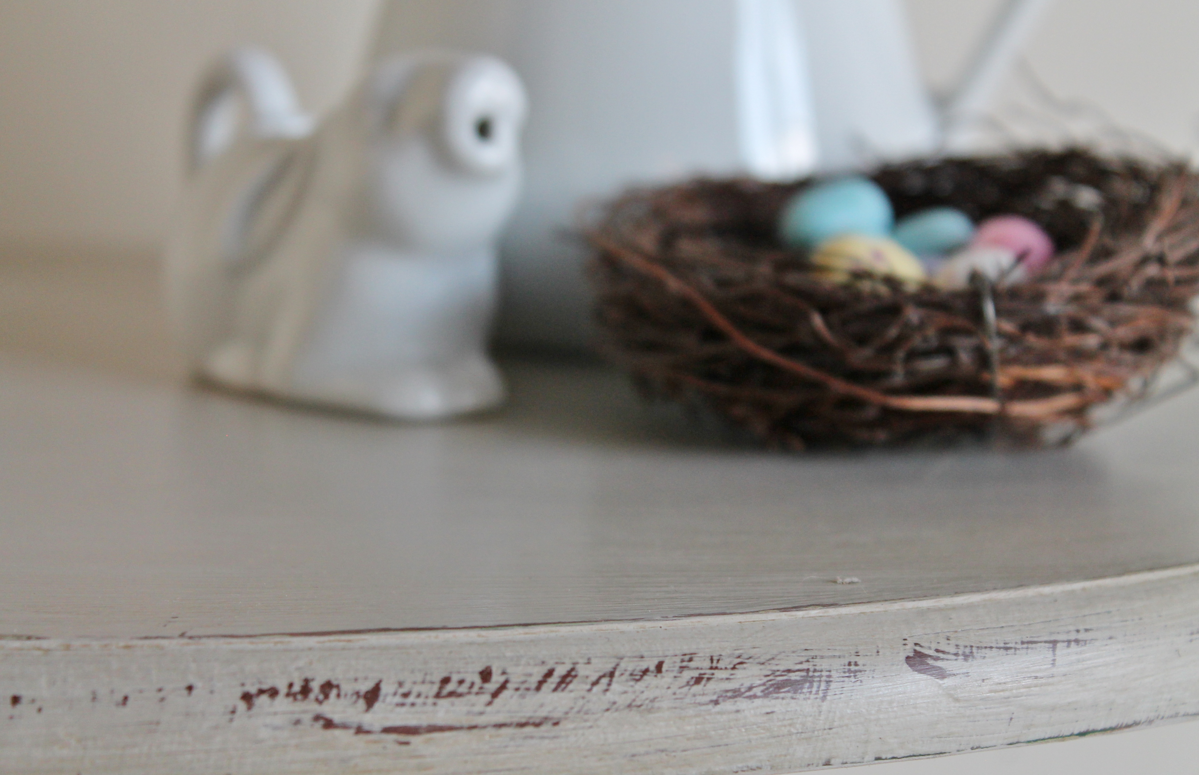 Chalk painted table staged with ironstone and bird's nest