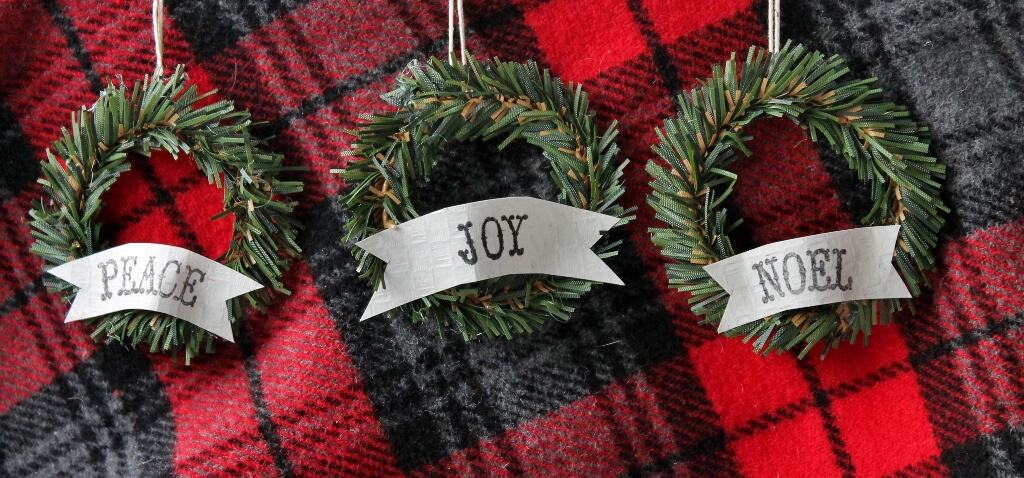 Three vintage-y mini wreaths displayed on red and black plaid wool fabric background