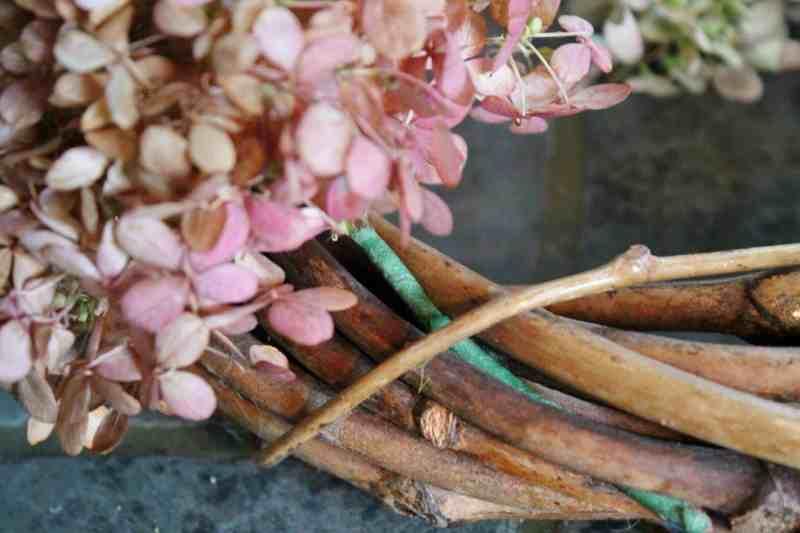 tucking hydrangea stem into wreath