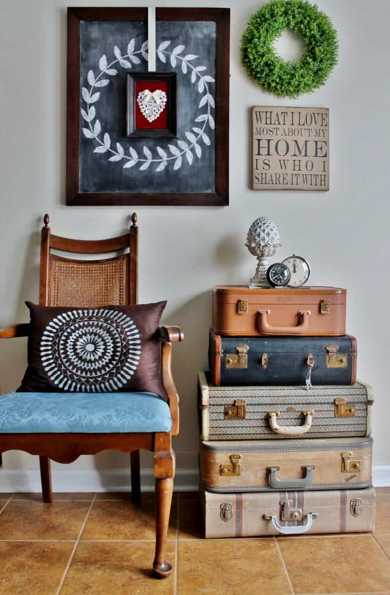 vintage luggage stack staged with vintage chair and gallery wall