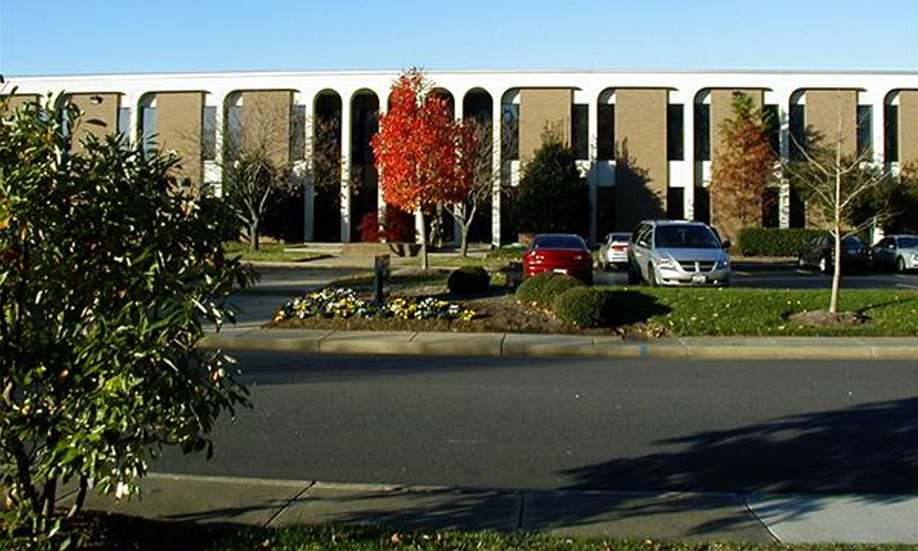 Office building with parking lot and fall foliage.