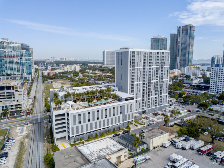 Midtown Miami aerial view of midrise apartment building with rooftop pool and city in the distance.