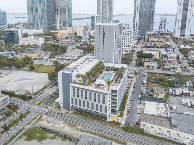 Midtown Miami aerial view of midrise apartment building with rooftop pool and ocean in the distance.
