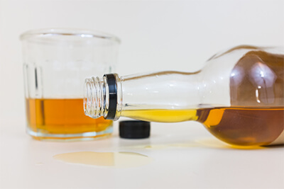 close up of alcohol bottle spilling with glass