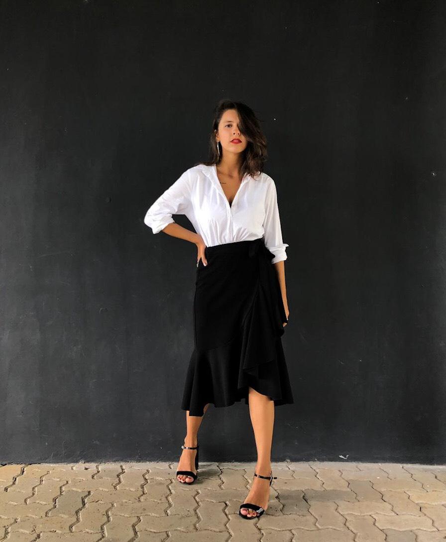 Garota posando em uma parede preta com um look preto e branco. O visual está composto por uma camisa branca clássica, saia mídi preta com babados na lateral e na barra e sandália preta de tiras finas