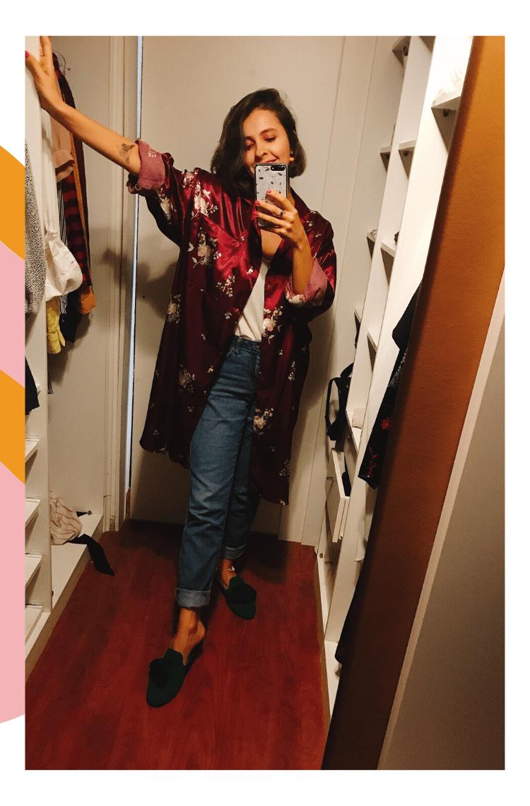 Montagem vertical com foto central e borda branca com detalhes rosa e laranja. Na foto, Marcie posa em frente a um espelho, com as prateleiras de um closet branco de fundo. O look é composto por calça jeans com barra dobrada, camiseta branca com gola v e quimono acetinado roxo com estampa floral por cima, além de mule verde com pompom azul.
