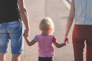 little girl in pink holding adults hands