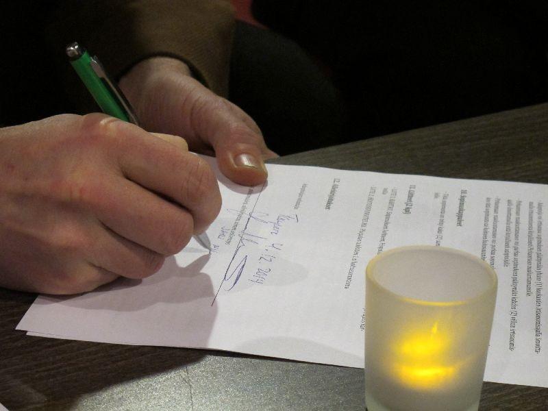Käsi kirjoittaa allekirjoitusta adoptiosopimukseen.