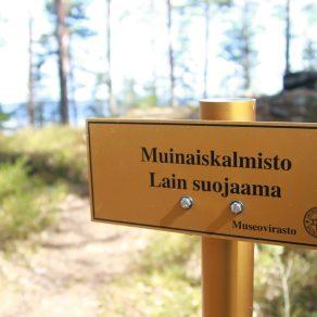 Muinaisjäännöskyltti Reuharinniemen röykkiöllä.