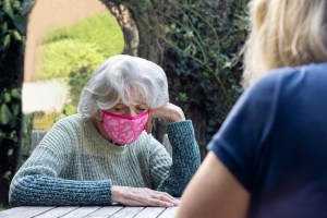 Image: Mature Woman Wearing Mask Visiting Lonely Depressed Senior Mother In Garden During Lockdown
