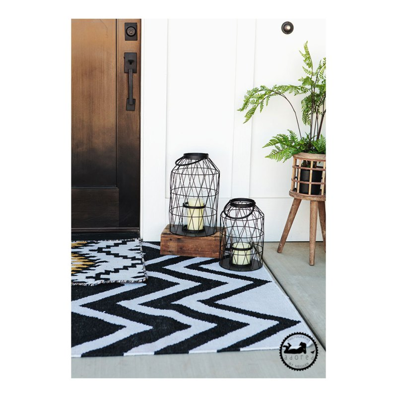 Layered rugs at front door, funky cage lanterns with battery operated candles, plant