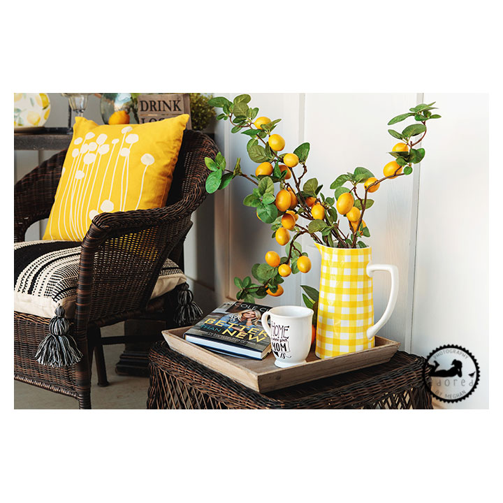 Front porch decor with sitting chair and side table, decorated with yellows and blacks.
