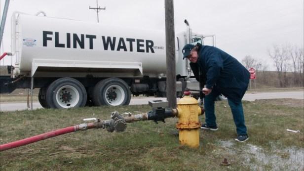 Szenenbild aus FAHRENHEIT 11/9 (2018) - Moore zapft vergiftetes Wasser aus dem Flint River. - © Weltkino