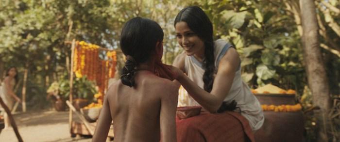 Szenenbild aus MOWGLI (2018) - Messua (Freida Pinto) nimmt Mogli im Dorf auf. - © Netflix