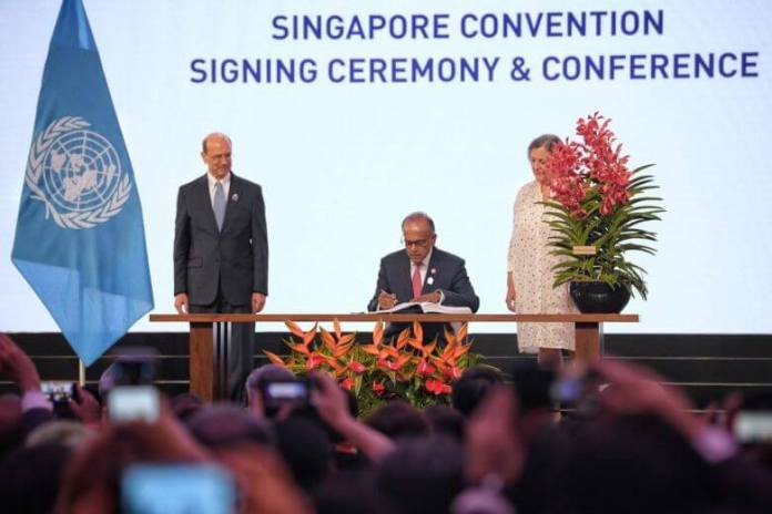 Home Affairs and Law Minister K. Shanmugam signing the Singapore Convention