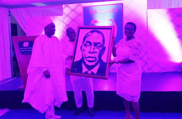 Mr Gamey (left) receiving a painting gift from the executives of Standard Chartered Bank Ghana