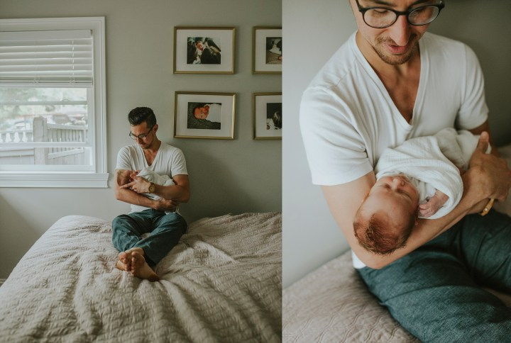 dad holding his new baby in bed