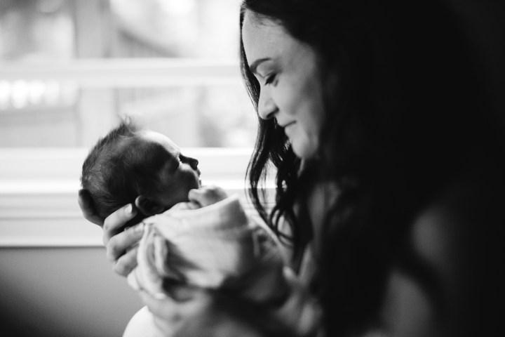 mom holding her new baby girl near a window freelensed
