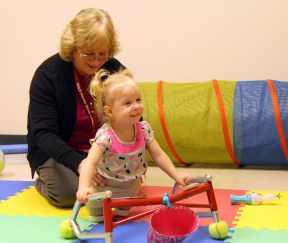 """Physical Therapist Bridget Jedlovec monitors MacKenzie's movements with her """"stumps"""" and walker"""