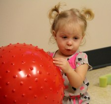 MacKenzie plays with a ball in the CRS sensory room