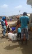 Le chantier solidaire continue. Nous remplissons des bidons d'eau pour fabriquer du ciment.