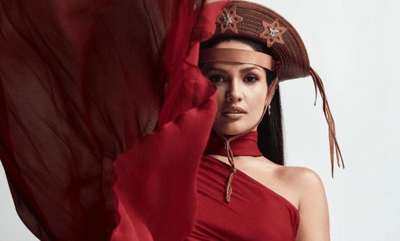 De cabelos soltos e lisos, Juliette usa um gibão de cangaceiro na cabeça e um vestido vermelho intenso esvoaçante