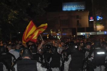 A protester wave a state flag in front of the police cordon after riot police disperse protesters from the park toward the pavement and boulevard.