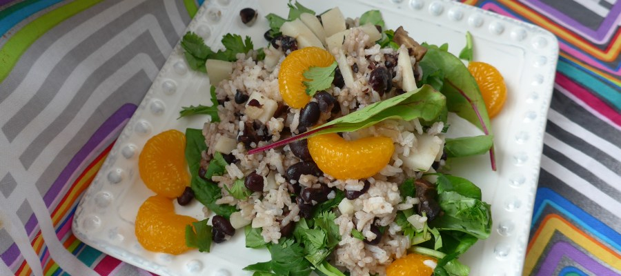 White square plate with dots on the edges, with a green salad topped with a rice mixture and bright mandarin oranges