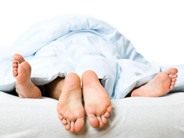 couples toes sticking out of bed