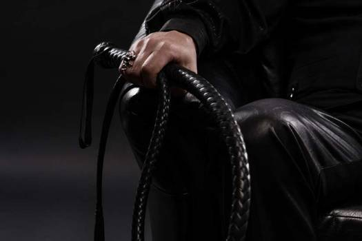 Confident Man With Leather Whip Sitting Down Photo