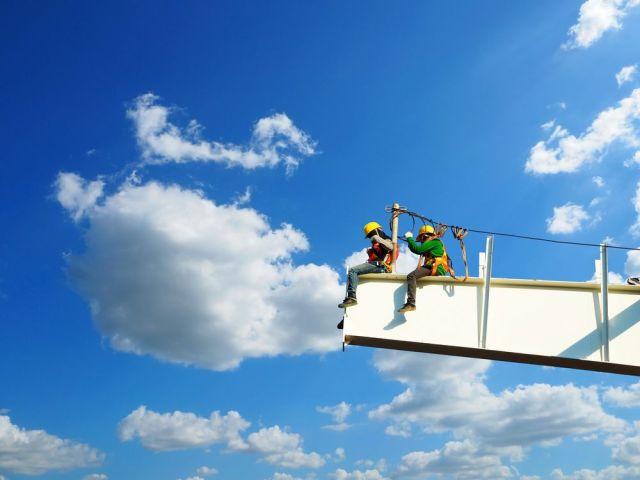dos hombres que trabajan en alturas en el sitio de construcción