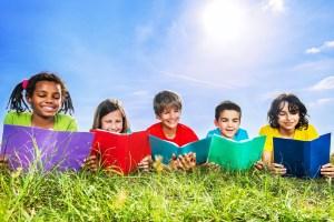 Children reading books in field