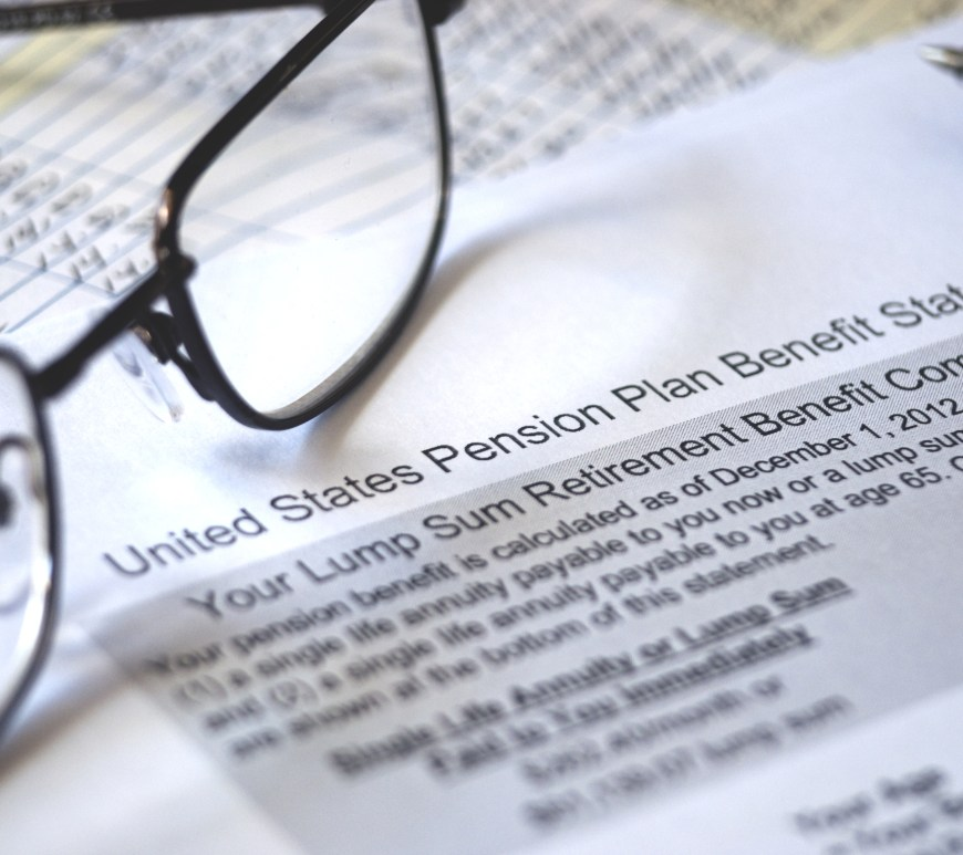 Pension plan paperwork with glasses resting on them.