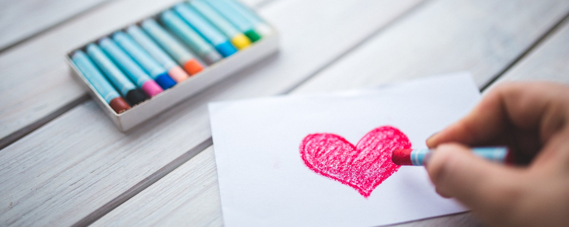 Hand drawing a heart in crayon.