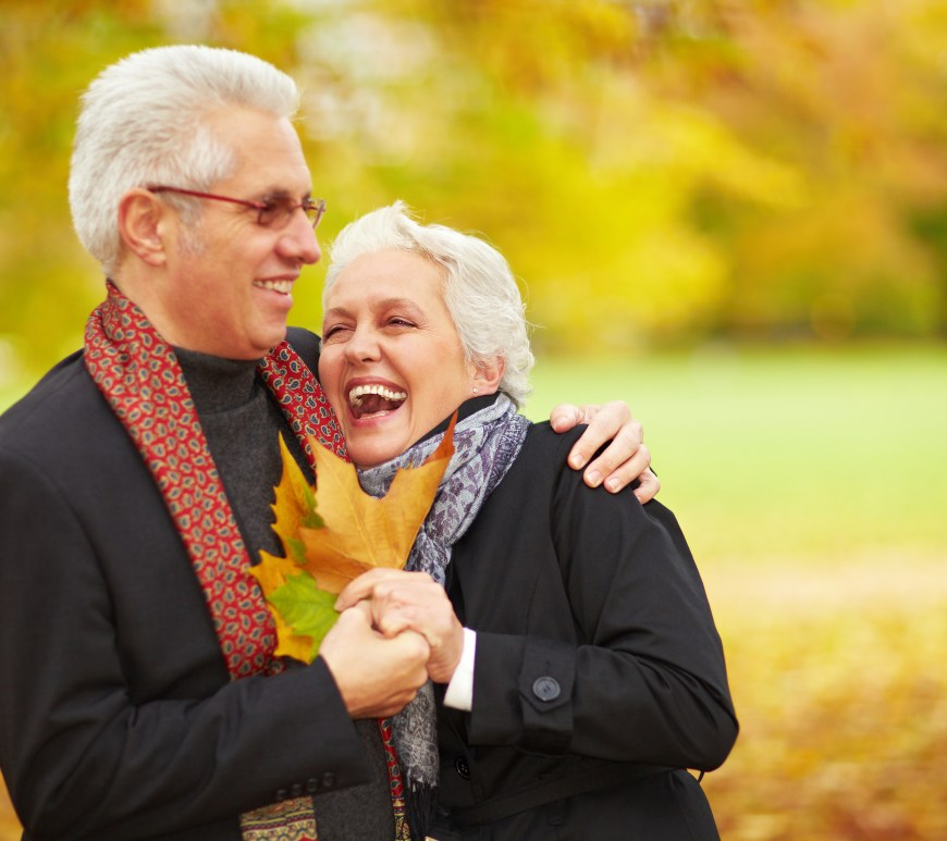 Man and woman hugging and holding leaves outside.