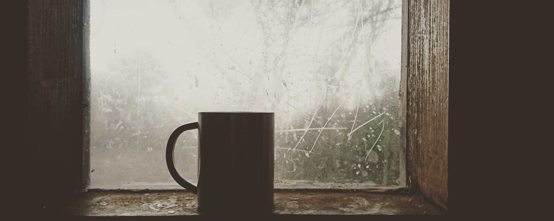 A coffee mug sits on a frosty window sill.