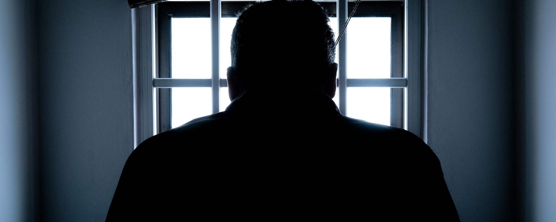 Silhouette of a man standing in front of a window.