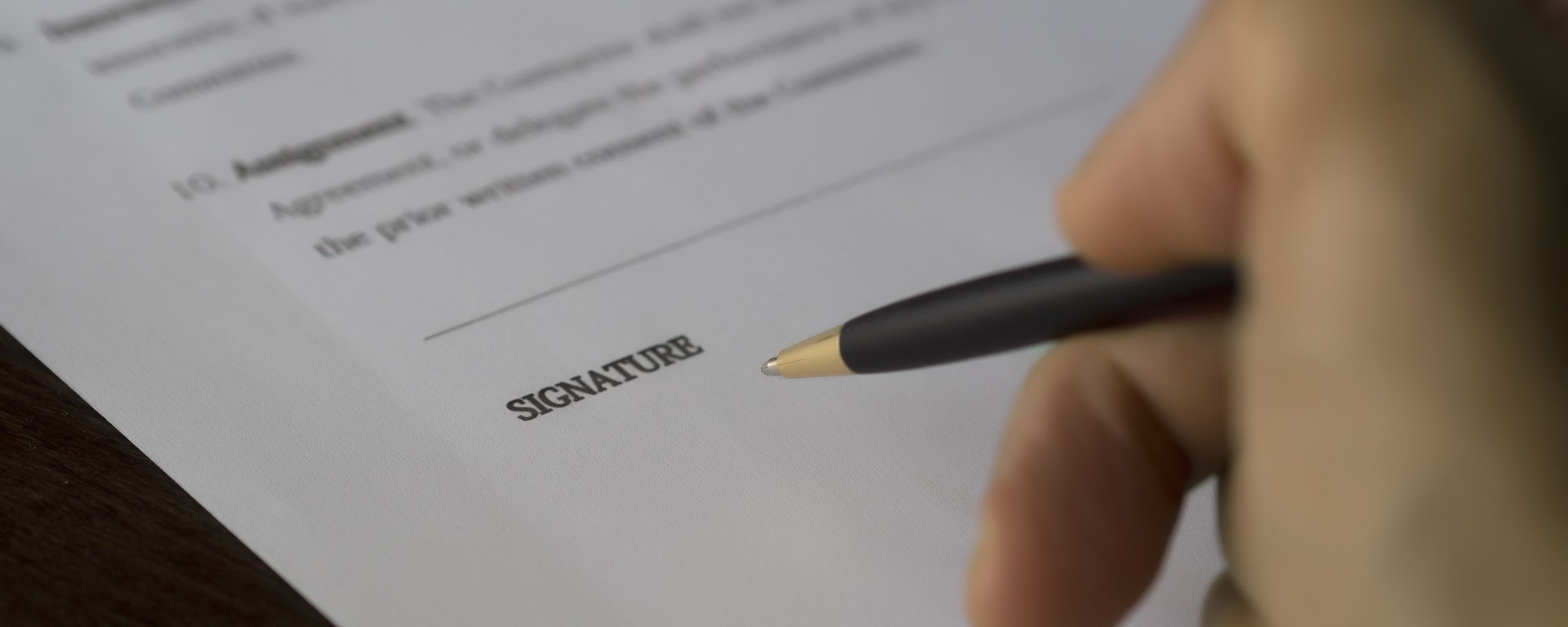 A hand holding a pen next to the signature line on a document.
