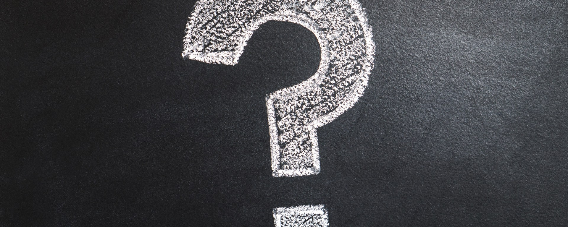 A question mark drawn in white chalk on a blackboard.