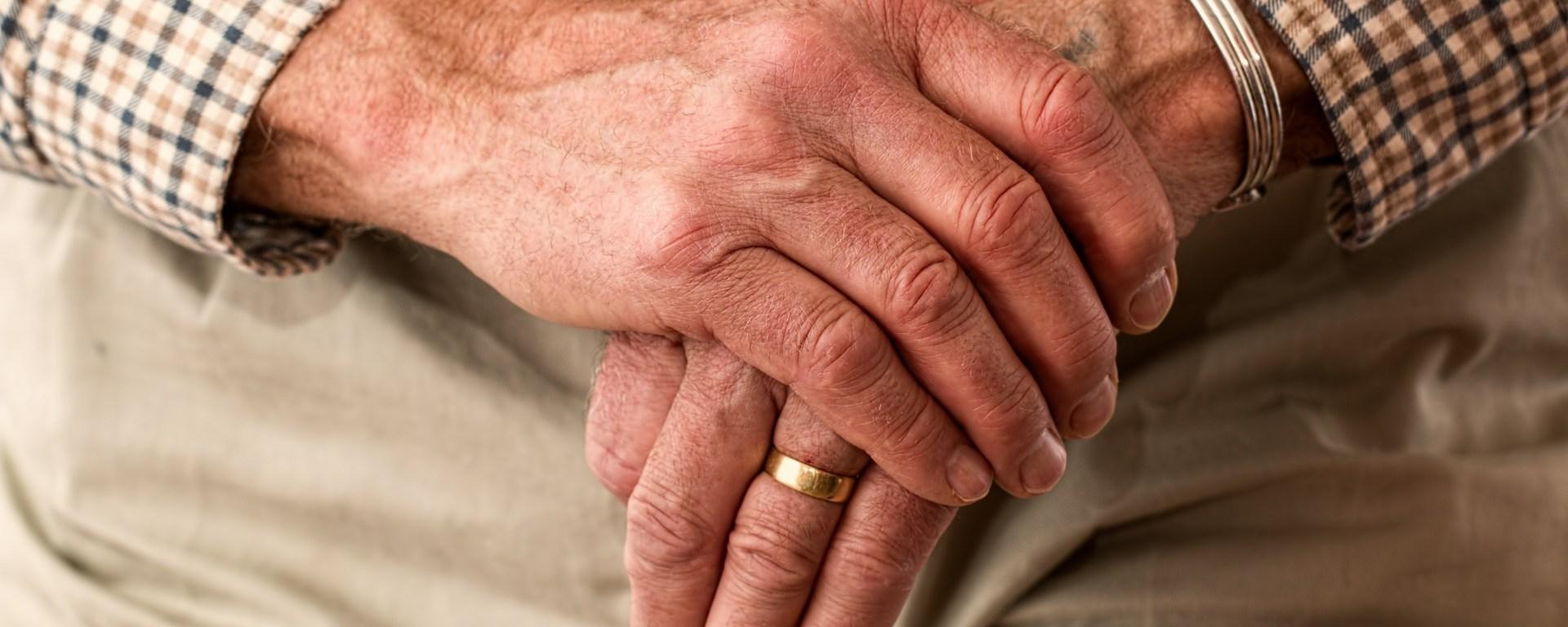 An elderly man's hands rest on top of a wooden cane.