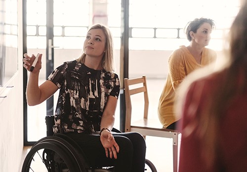 A woman using a wheelchair looks up at a dry erase board.