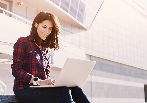 A woman wearing a plaid shirt uses a laptop.