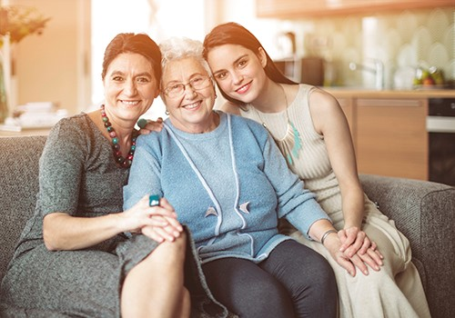Three generations of women sit together on a couch.